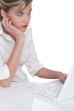 Frau, die mit Laptop und der Aufwartung arbeitet Stockfotos