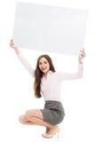 Frau, die mit leerem Zeichen sich duckt Stockbilder