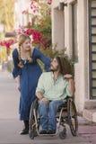 Frau, die mit Mann im Rollstuhl plaudert Lizenzfreie Stockfotografie