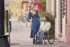 Frau, die mit Mann im Rollstuhl spricht Lizenzfreie Stockfotos
