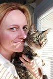 Frau, die mit Miezekatze-Katze Snuggling ist Stockfotografie