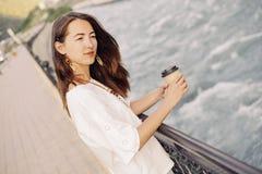Frau, die mit Mitnehmerkaffee auf Damm von Fluss geht lizenzfreies stockfoto
