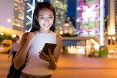 Frau, die mit Mobiltelefon nachts hält Stockfotos