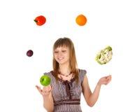 Frau, die mit Obst und Gemüse jongliert Stockfotos
