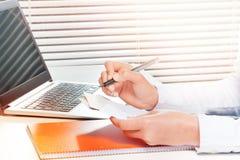 Frau, die mit Papieren arbeitet und Anmerkungen macht Stockbild