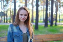Frau, die mit perfektem Lächeln in einem Park lächelt und Kamera betrachtet Lizenzfreie Stockbilder