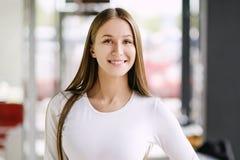 Frau, die mit perfektem Lächeln und den weißen Zähnen in einem Mall betrachtet Kamera lächelt stockfoto