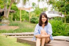 Frau, die mit perfektem Lächeln und den weißen Zähnen im Park lächelt und Kamera betrachtet Stockfotos