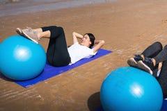 Frau, die mit pilates Ball auf dem Strand trainiert lizenzfreies stockfoto