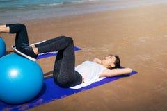 Frau, die mit pilates Ball auf dem Strand trainiert stockfotos