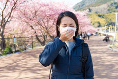 Frau, die mit Pollenallergie unter Kirschblüte-Baum unwohl sich fühlt Stockbilder