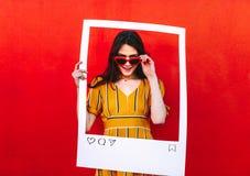 Frau, die mit Posten-Fotorahmen des Sozialen Netzes aufwirft lizenzfreie stockfotos