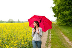 Frau, die mit Regenschirm geht Stockfotografie