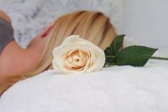 Frau, die mit rosafarbener Blume auf Bettkissenabschluß oben schläft Selektiver Fokus auf Blume Überraschungsgeburtstagsgeschenk Lizenzfreie Stockfotografie