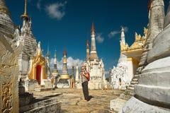 Frau, die mit Rucksack und Blicken an stupas Buddhist templ reist Lizenzfreie Stockfotos