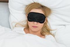 Frau, die mit Schlafmaske schläft Lizenzfreies Stockfoto
