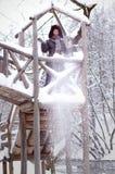 Frau, die mit Schnee in einem Wald spielt Stockfotografie