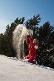 Frau, die mit Schnee spielt Lizenzfreie Stockfotografie