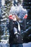 Frau, die mit Schnee spielt Stockfotografie