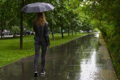 Frau, die mit schwarzem Regenschirm unter den Regen in einem Park geht lizenzfreie stockfotografie