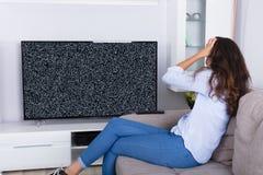 Frau, die mit Störschub Fernsehschirm frustriert lizenzfreies stockbild