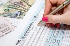 Frau, die mit Steuerformulardokumenten mit Geld arbeitet Stockfoto