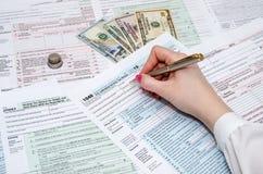 Frau, die mit Steuerformulardokumenten mit Geld arbeitet Stockfotografie