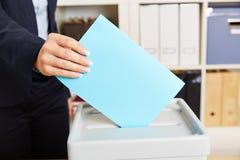 Frau, die mit Stimmzettel auf Kasten wählt Lizenzfreies Stockfoto