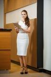 Frau, die mit Tablette steht und im Rahmen schaut lizenzfreie stockfotos