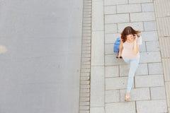 Frau, die mit Tasche geht und am Handy spricht Lizenzfreies Stockbild