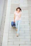 Frau, die mit Tasche geht und am Handy spricht Lizenzfreie Stockbilder