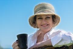 Frau, die mit Tasse Kaffee im Garten sitzt Stockfotografie