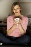 Frau, die mit Tasse Kaffee sich entspannt Lizenzfreie Stockfotografie