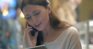 Frau, die mit Telefongespräch beschäftigt und Auflage im Café verwendet worden sein würden stock footage