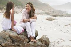Frau, die mit Tochter auf Felsen sitzt Stockfotos