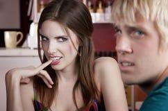 Frau, die mit unintereßiertem männlichem Freund flirtet Stockbilder