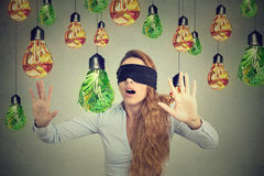 Frau die mit verbundenen Augen, die durch Glühlampen geht, formte als Grüngemüse der ungesunden Fertigkost stockfotografie