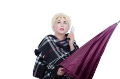 Frau, die mit violettem Regenschirm auf weißem Hintergrund aufwirft Lizenzfreies Stockfoto