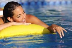 Frau, die mit Wasser auf einem Swimmingpool in Ferien badet und spielt Lizenzfreies Stockbild