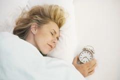 Frau, die mit Wecker schläft Lizenzfreies Stockbild