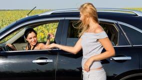 Frau, die mit weiblichem Treiber im Auto spricht Stockbilder
