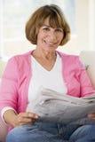 Frau, die mit Zeitung im Wohnzimmer sich entspannt Stockbild