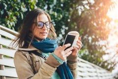 Frau, die Mitnehmerkaffee hält und intelligentes Telefon verwendet Lizenzfreie Stockfotografie