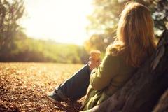 Frau, die Mitnehmerkaffeetasse am sonnigen kalten Falltag genießt Stockfotografie