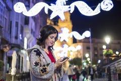 Frau, die Mitteilungen des Sozialen Netzes in Winter chri sendet und schaut Lizenzfreie Stockfotos