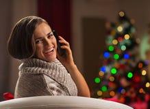 Frau, die Mobile vor Weihnachtsbaum nennt Stockfotografie