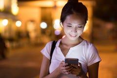 Frau, die Mobiltelefon am Abend bei Hong Kong betrachtet lizenzfreie stockbilder