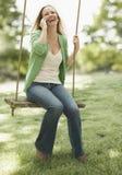 Frau, die Mobiltelefon auf einem Schwingen verwendet Stockfotos