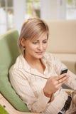 Frau, die Mobiltelefon im Lehnsessel verwendet Stockbilder