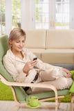 Frau, die Mobiltelefon im Lehnsessel verwendet Lizenzfreies Stockfoto